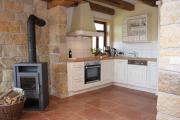 Wohnküche mit Sandsteinwänden und alten Holzbalken