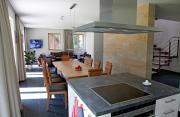 Wohnzimmer mit offener Küche und Kamin